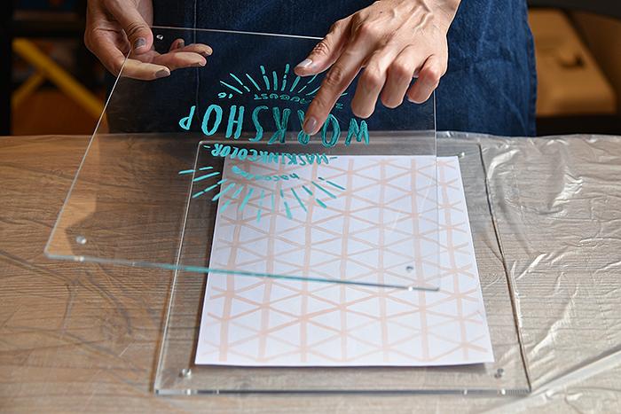乾燥後にアクリル板2枚の間に背景用紙を中央に配置して挟みます。
