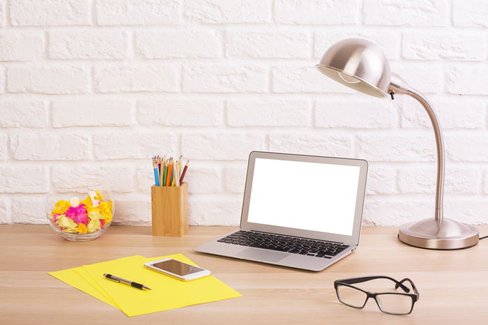 Closeup of creative designer desktop with blank white laptop, smart phone, glasses, table lamp, stationery and decorative items on brick wall background. Mock up