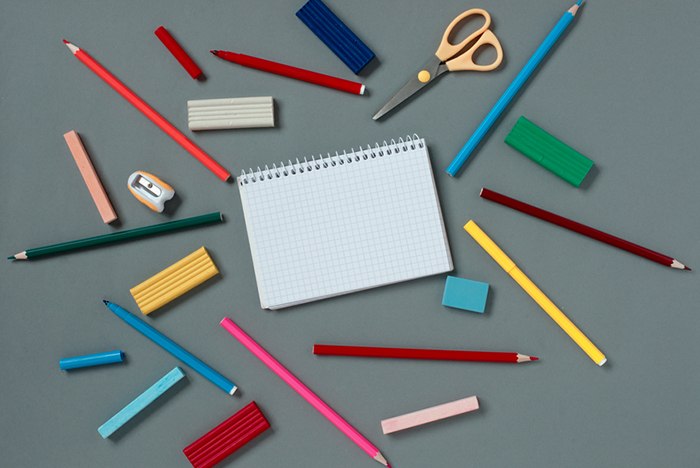 View from above of an open blank notebook surrounded with scattered assorted stationery supplies and writing implements on a grey background