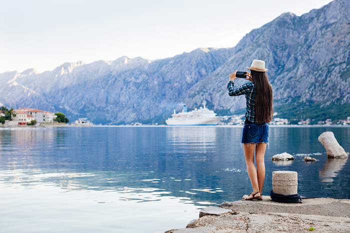 girl taking photo on smartphone of cruise liner yacht in picturesque landscape bay water bakground view