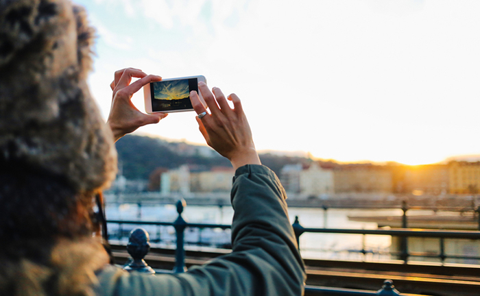 Young woman is walking on the streets of Budapest, by the river Danube. She is using her smartphone to take a photo of a beautiful sunset over the river. She is wearing winter clothes, a Russian style fur hat and a jacket.