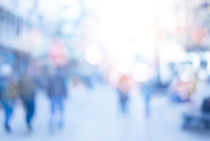 A crowd of people moving on street, defocused blurred abstract image with bokeh lights, blue tone