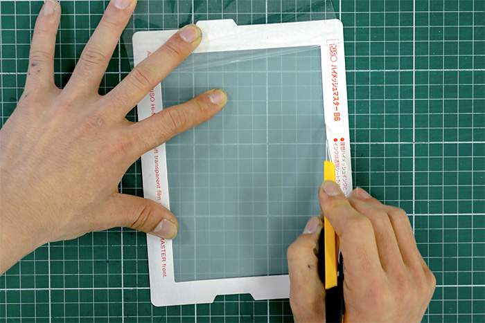 プリントゴッコ用の「ハイメッシュマスターB6」は、フレームの表面が白色で裏面が水色です。表面(白色)を上にして、無地のシルクスクリーン部分のフチをカッターでカットします。