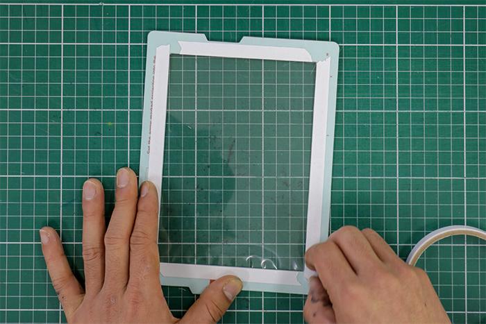 裏面(水色)を上にして、フレームの内側に両面テープ(約1cm幅)を貼り、白いはくり紙を剥がします。
