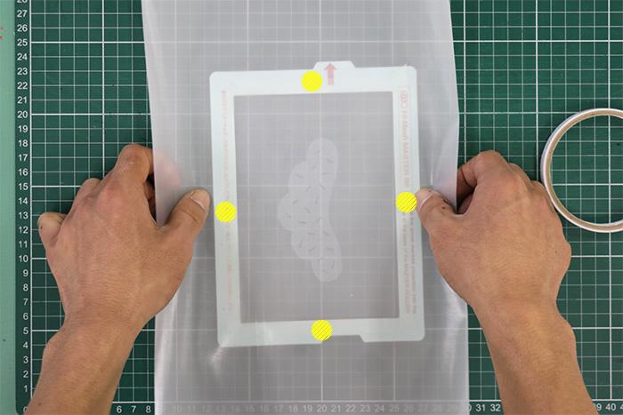 印刷が反転するようツルツル面を上にし、黄色いポイントを指で押さえながら、きれいにピンと張っていきます。