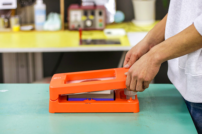 本体上部の圧版のプッシュポイントを押して印刷します。試し刷りが成功したら手ぬぐいをプリントパッドにセットしましょう。プリントゴッコは、プッシュポイントの押し加減や、絵柄の違いなどで、印刷の濃さが微妙に変わります。
